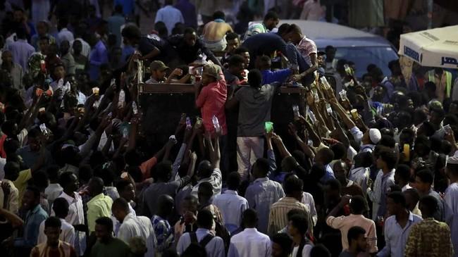 Di Sudan, umat Muslim menunggu minuman bersoda gratis setelah berbuka pada hari pertama puasa di bulan suci Ramadan 1440 H, Senin (6/5). (REUTERS/Umit Bektas)