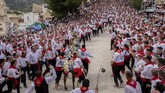 Peraturan dalam festival ini sederhana saja. Empat pria memakai celana hitam, kemeja putih dan syal merah berlari di sebelah kuda, menggantung di atasnya saat ia berlari menaiki jalan yang curam menuju kastil.(AP Photo/Bernat Armangue)