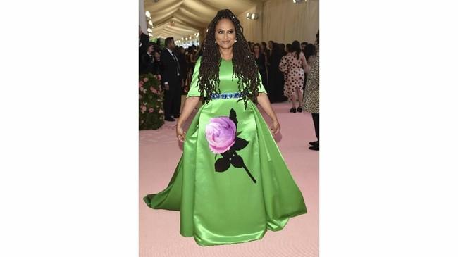 Bak batu jamrud, sutradara Ava DuVernay mengenakan gaun Prada hijau terang. Potongannya tampak biasa, tetapi detail setangkai mawar merah muda pada bagian depan terlihat cukup mengganggu. (Photo by Evan Agostini/Invision/AP)