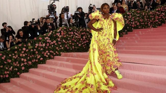 Serena Williams ikut mencuri perhatian publik di Met Gala 2019. Petenis satu ini tampil mengenakan gaun off-shoulder Versace berwarna kuning menyala berhias daun-daun merah muda. Gaun cantik itu dipadukan secara sempurna dengan sneakers putih kolaborasi Nike dan Off-White. (REUTERS/Andrew Kelly)