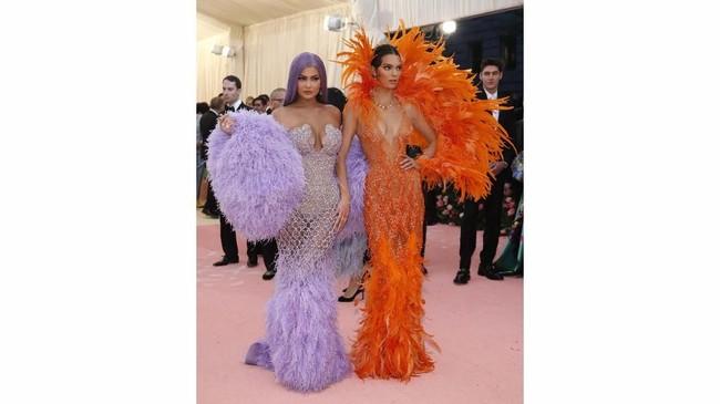 Kali ini, Kendall dan Kylie Jenner tampil 'kembar'. Keduanya kompak mengenakan gaun berbulu terang yang terinspirasi oleh penyanyi Cher. Kendall mengenakan gaun berbulu oranye, sementara Kylie hadir dengan bulu-bulu lavendernya. (REUTERS/Mario Anzuoni)
