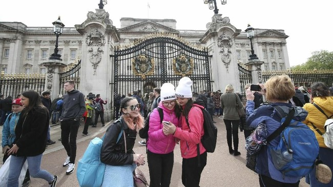 Para pendukung Kerajaan Inggris pun bersuka cita atas kedatang anak berjenis kelamin laki-laki itu. Mendadak, Istana Buckingham pun kedatangan turis yang ingin melihat pengumuman tersebut.(Yui Mok/PA via AP)