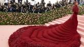 Bak burung raksasa berjalan, Cardi Bmenyapuh karpet merah dengan gaun panjang dan lebar berwarna merah lengkap dengan detail bulu berwarna serupa. Tampilan juga dilengkapi oleh headpiece berhiaskan berlian merah dan sarung tangan warna senada. (REUTERS/Andrew Kelly)