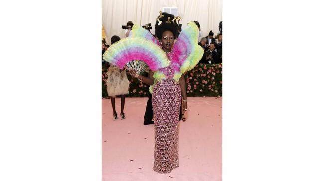 Lupita Nyong'o tak menghindari warna cerah. Dia hadir dengan gaun merah muda berlengan ruffle tebal dengan warna-warni neon buatan Versace. Tak cuma itu, Nyong'o juga menyematkan sejumlah sisir tipis pada rambut tebal dan keritingnya sebagai simbol kekuatan dan kemewahan rambut alami. (REUTERS/Andrew Kelly)