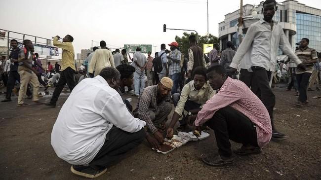 Para pemrotes Sudan yang tengah berada dalam konflik berbagi jamuan berbuka puasa di hari pertama bulan suci Ramadan di luar markas militer di Khartoum, Senin (6/5). (Mohamed el-Shahed / AFP)