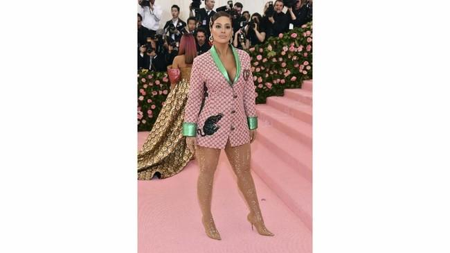 Ashley Graham tampil cukup mencolok dengan balutan blazer Gucci pink dan detail hijau neon. Perpaduan dengan legging warna kulit membuatnya seolah lupa mengenakan celana. (Photo by Charles Sykes/Invision/AP)