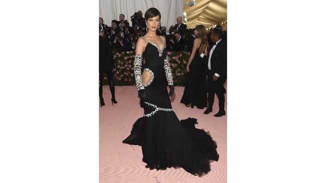 Model Bella Hadid menghadiri Met Gala tanpa ditemani sang kekasih, The Weeknd. Ia ditemani taburan permata pada gaun hitamnya. Potongan di pinggul terlihat cukup mengganggu dan menimbulkan asumsi ia tak mengenakan celana dalam. (Photo by Evan Agostini/Invision/AP)