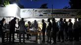 Umat muslim mengantre sajian takjil dan makan untuk berbuka puasa setelah matahari terbenam di Masjid At-Tawheed, Port-au-Prince, Haiti, Senin (6/5). (CHANDAN KHANNA/AFP)