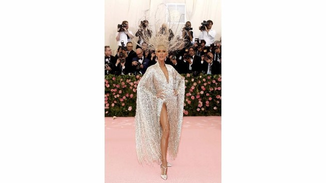 Celine Dionmengenakan bodysuit berwarna perak yang dihiasi manik-manik warna serupa rancangan Oscar de la Renta. Semakin berkilau dengan lengan yang terbungkus oleh 3 ribu helai tali yang terbuat dari manik-manik kecil. Tampilan juga dilengkapi dengan headpiece berbulu emas karya Noel Stewart. (REUTERS/Andrew Kelly)