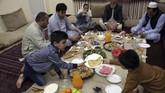 Keluarga asal Afghanistan berbuka puasa penuh hangat menyantap sajian takjil di hari pertama bulan suci Ramadan di Kabul, Afghanistan, Senin (6/5). (AP Photo/Rahmat Gul)