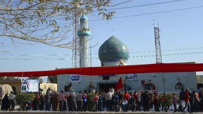 Warga Syiah Irak berkumpul di depan masjid setempat di Midhatiya, 60 mil di selatan Baghdad. (Haidar HAMDANI / AFP)