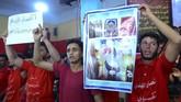Para pemuda Syiah Irak mengangkat poster dan spanduk bertuliskan pesan persatuan agama. (Haidar HAMDANI / AFP)