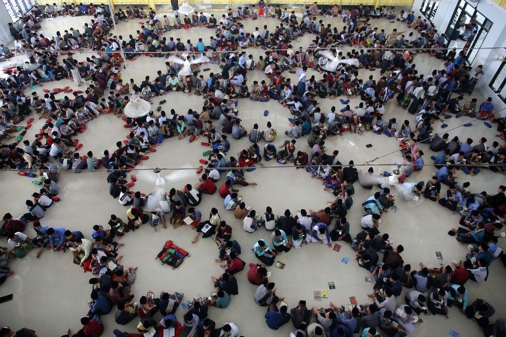 Murid-murid dari pondok pesantren Ar-Raudlatul Hasanah duduk berputar-putar ketika mereka membaca Alquran saat bulan puasa Ramadan di sebuah masjid di Medan, Sumatera Utara, Indonesia. (REUTERS / Ahmad Ridwan Nasution)