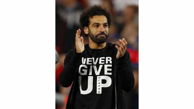 Winger Mohamed Salah menjadi sorotan karena menggunakan t-shirt bertulisan 'Jangan pernah menyerah' ketika harus absen saat Liverpool mengalahkan Barcelona. (REUTERS/Phil Noble)