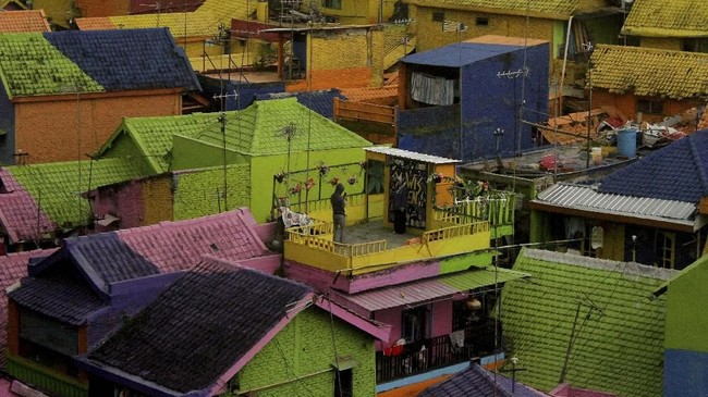 Pengunjung memotret rekannya di Kampung Warna-Warni, Jodipan, Malang, Jawa Timur, Selasa (7/5). (ANTARA FOTO/Ari Bowo Sucipto)