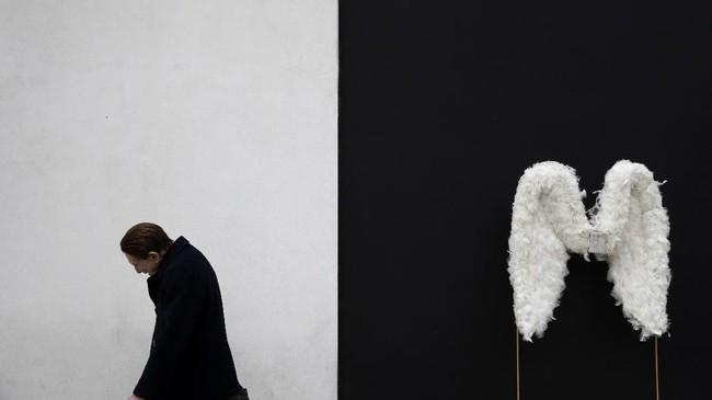 Seorang pria berjalan melewati sepasang sayap malaikat yang dipajang di suatu toko di Beverly Hills, California, Amerika Serikat. (AP Photo/Jae C. Hong)