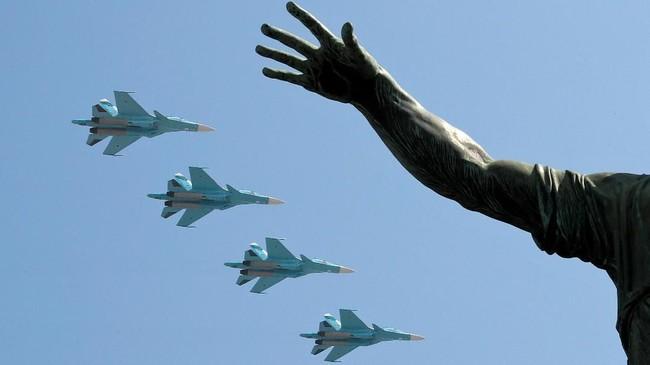 Di Lapangan Merah, Moskow, Rusia, jet tempur Sukhoi-34 terbang melintasi monumen Kuzma Minin dan Dmitry Pozharsky pada gladi resik jelang parade hari kemenangan. Perayaan itu digelar untuk mengingat kemenangan atas Nazi di PErang Dunia II. (REUTERS/Shamil Zhumatov)