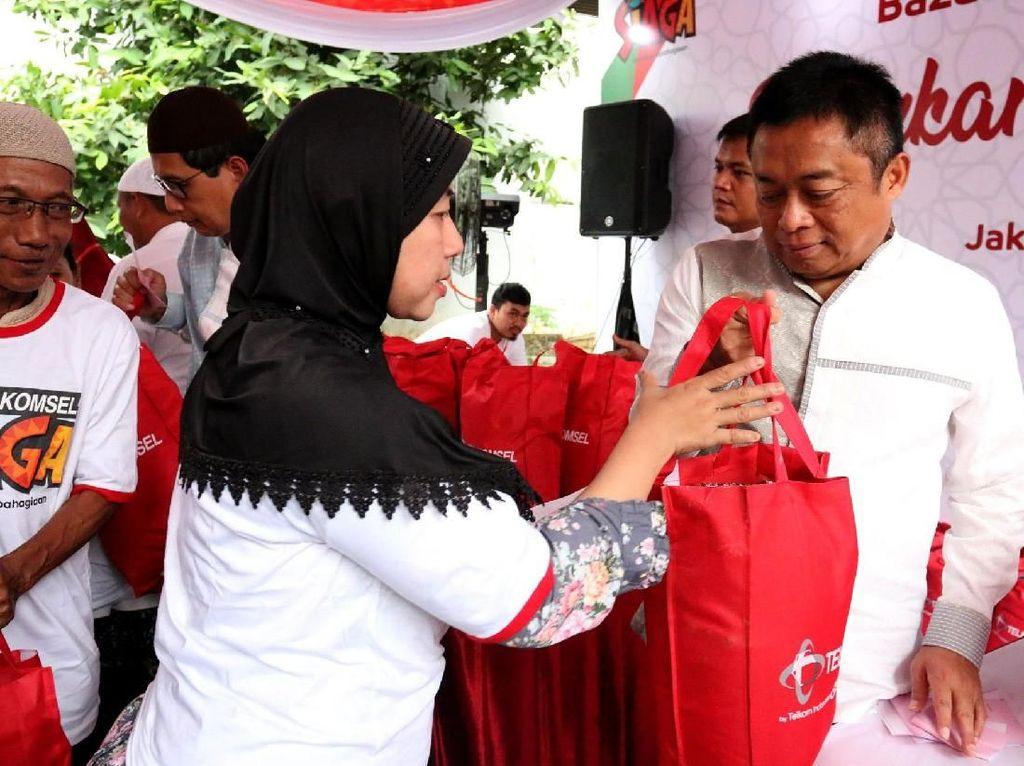 Direktur Utama Telkomsel Ririek Adriansyah saat melayani warga yang berpartispasi dalam kegiatan Bazaar Sembako Murah di Jakarta. Foto: dok. Telkomsel