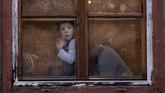 Bocah berusia satu tahun menatap keluar dari balik jendela yang dipenuhi air hujan di kota Sibiu, Rumania. Sibiu sendiri akan menjadi kota penyelenggara pertemuan kepala negara Uni Eropa. (AP Photo/Vadim Ghirda)
