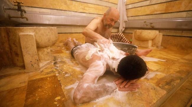Mereka mandi menggunakan sabun khas Aleppo yang terbuat dari zaitun dan daun salam. Mereka membilas tubuh dengan air panas dari sebuah mangkuk yang diambil dari bak mandi besar yang terbuat dari bebatuan. (REUTERS/Omar Sanadiki)