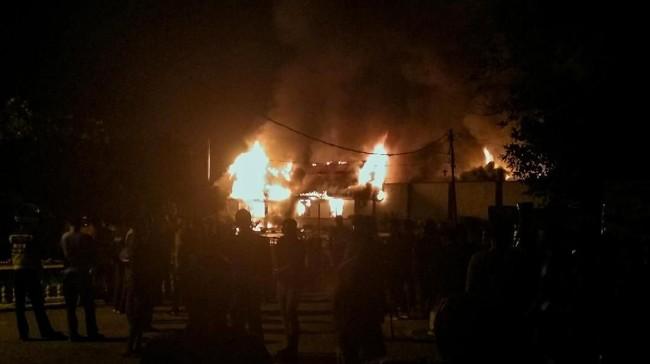Warga menyaksikan Rumah Tahanan Negara (Rutan) Klas IIB Siak Sri Indrapura terbakar di Kabupaten Siak, Riau, Sabtu (11/5). Narapidana dantahanan mengamuk dan membakar Rutan sekitar pukul 02.00 WIB. (ANTARA FOTO/Bayu Agustari Adha/FBA/wpa).