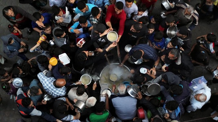 Buka Puasa di Berbagai Negara (Palestinians gather to get soup offered for free during the Muslim fasting month of Ramadan, in Gaza City May 9, 2019. REUTERS/Mohammed Salem)