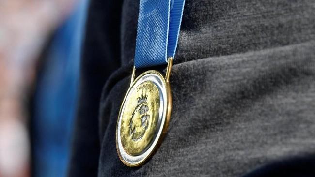 Medali gelar juara Liga Inggris yang melingkar di leher Pep Guardiola. (REUTERS/Toby Melville)