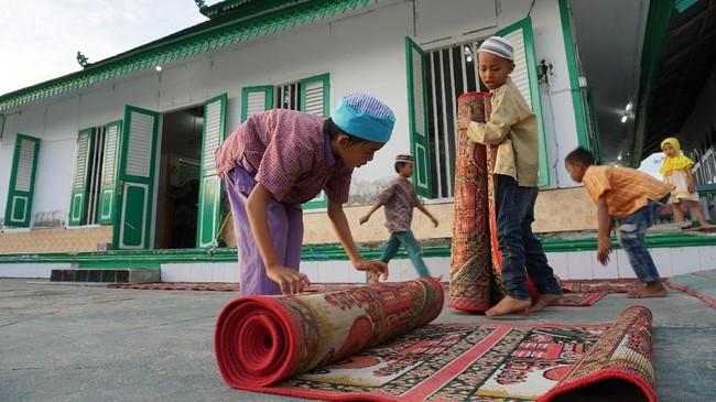 Sejumlah anak menyiapkan tempat berbuka puasa di Situs Cagar Budaya Masjid Al Amin atau biasa dikenal Masjid Tua Wani di Desa Wani, Kabupaten Donggala, Sulawesi Tengah, yang dibangun pada 1906 dan tetap kokoh meski terdampak gempa dan tsunami pada 28 September 2018. (ANTARA FOTO/Mohamad Hamzah/pd.)
