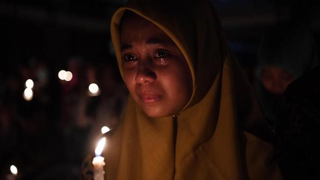 Seorang umat muslim meneteskan air mata ketika mengikuti doa bersama lintas agama saat peringatan setahun tragedi bom gereja Surabaya di Gereja Katolik Santa Maria Tak Bercela, Surabaya, Jawa Timur, Senin (13/5/2019). Pada peringatan tersebut digelar juga doa lintas agama yang dihadiri sejumlah pemuka agama. ANTARA FOTO/Zabur Karuru/wsj.