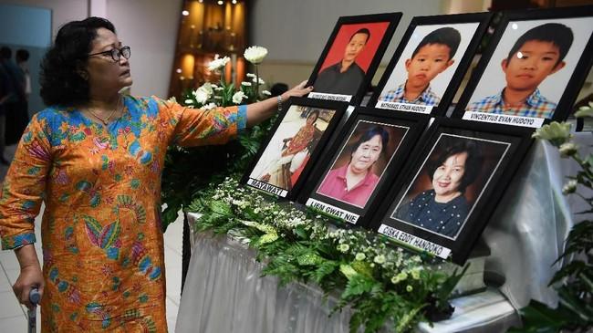 Seorang perempuan mengamati foto-foto korban tragedi bom gereja Surabaya usai mengikuti misa peringatan tragedi tersebut di Gereja Katolik Santa Maria Tak Bercela, Surabaya, Jawa Timur, Senin (13/5/2019). Pada peringatan tersebut digelar juga doa lintas agama yang dihadiri sejumlah pemuka agama. ANTARA FOTO/Zabur Karuru/wsj.