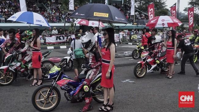 Seperti balapan MotoGP, road race di Indonesia juga menggunakan jasa gadis payung. Biasanya gadis payung hadir saat road race memasuki babak final. (CNN Indonesia/M Arby Rahmat)
