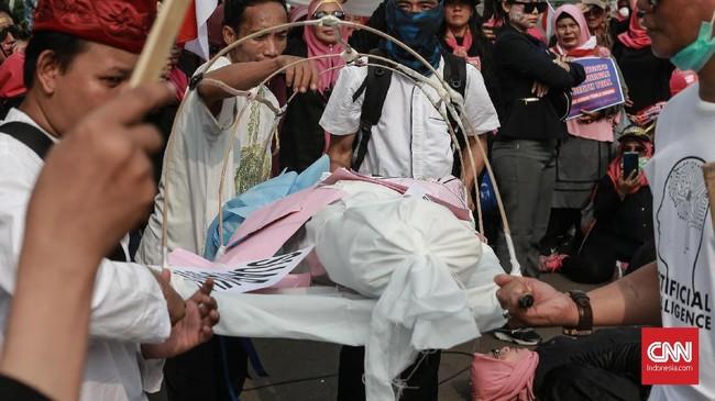 Aksi teatrikal menggotong keranda mayat sebagai simbol matinya demokrasi untuk para perempuan yang tergabung dalam Aksi PIB, di seberang IstanaMerdeka.(CNN Indonesia/Andry Novelino)