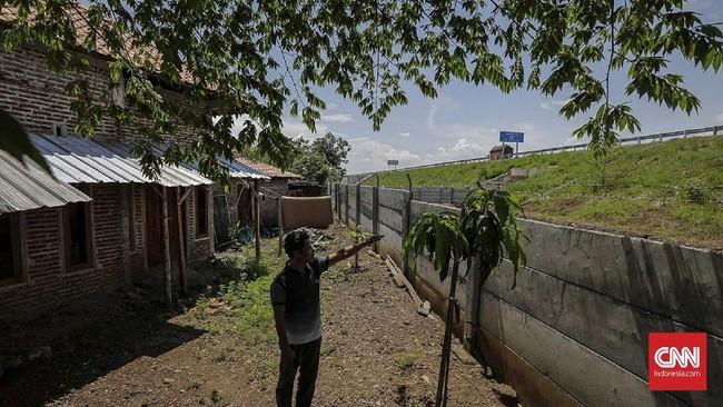 Aminudin, warga Desa Rejosari menunjukan rumah orang tuanya yang terhalang tembok pembatas jalan tol Trans Jawa ruas Semarang-Batang. Akses jalan ke rumah tersebut terhambat paska pelebaran area tol. (CNNINdonesia/Adhi Wicaksono).