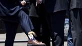 Gubernur Louisiana, Billy Nugesser, menunjukkan kaus kakinya kepada presiden AS Donald Trump setelah orang nomor satu di negeri Paman Sam itu tiba di bandara internasional Chennault. (Photo by Brendan Smialowski / AFP)