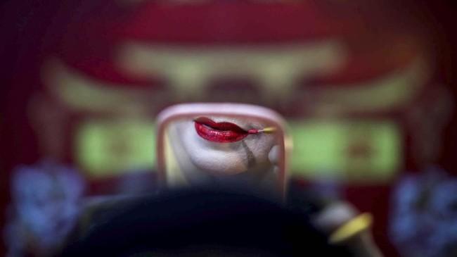 Seorang anggota kelompok opera tradisional China memulas tata rias sebelum tampil di suatu kuil di Bangkok, Thailand. (REUTERS/Athit Perawongmetha)