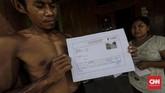 Seorang warga Desa Rejosari menunjukan surat nilai ganti rugi tanah dari notaris yang seharusnya dibayar untuk pembebasan lahan tol trans Jawa tahap ll atas sawah miliknya. (CNNINdonesia/Adhi Wicaksono).