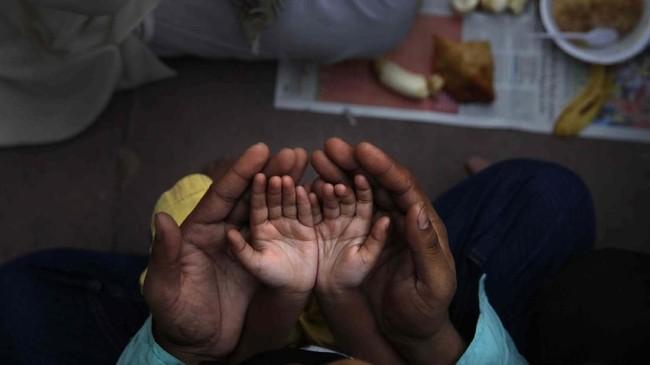 Di masjid Jama di New Delhi, India, seorang ayah memegang tangan putrinya ketika sama-sama berdoa sebelum berbuka puasa di hari pertama bulan Ramadan. (AP Photo/Manish Swarup, File)