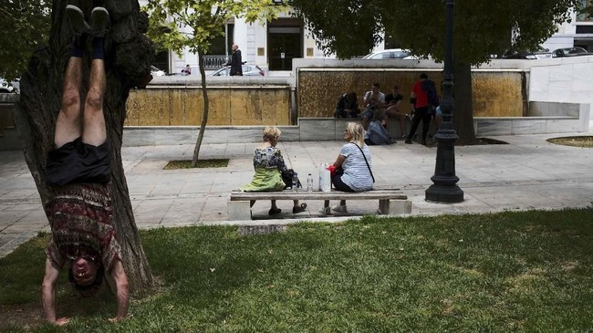Seorang pria berolahraga sementara orang-orang lainnya duduk di alun-alun Syntagma di Athena, Yunani. (REUTERS/Constantina Peppa)