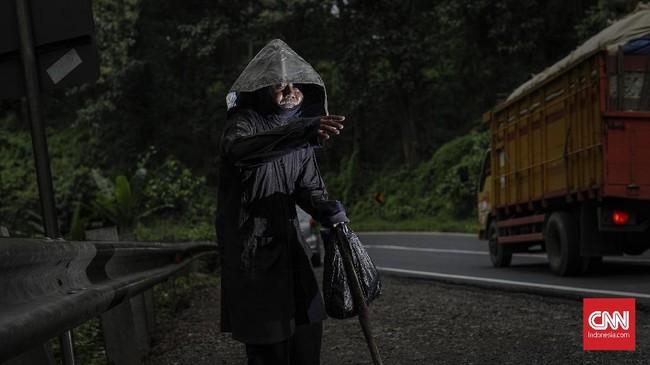 Di beberapa titik berdiri beberapa tunawisma mengenakan pakaian serba hitam dan muka tertutup, selalu melambaikan tangan minta sedekah ketika ada kendaraan yang melintas. (CNNIndonesia/Adhi Wicaksono).