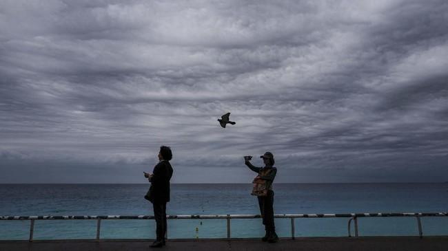 Seorang perempuan mengambil gambar di depan laut Mediterrania di kota Nice, Perancis. (Photo by VALERY HACHE / AFP)