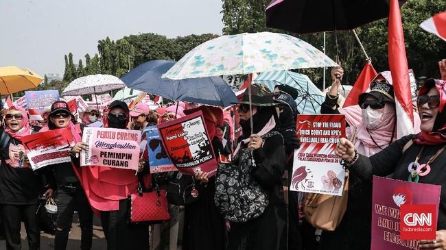 Ratusan perempuan itu mendatangi Istana dengan mengenakan pakaian hitam dan kerudung merah muda. (CNN Indonesia/Andry Novelino)
