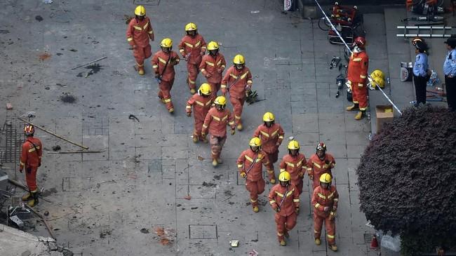 Petugas pemadam kebakaran dan tim penyelamat berkejaran dengan waktu untuk menyelamatkan korban. (Photo by Hector RETAMAL / AFP)