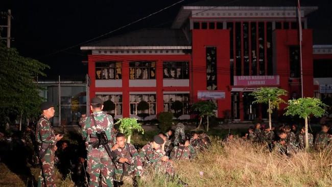 Prajurit TNI berjaga di depan Lapas Narkotika Kelas III Langkat, Sumatra Utara pasca kerusuhan, Kamis (16/5/2019). Kerusuhan tersebut mengakibatkan tiga mobil petugas rusak terbakar dan ratusan napi melarikan diri. ANTARA FOTO/Irsan Mulyadi/pras.