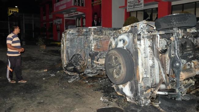 Seorang pria melihat bangkai mobil yang rusak akibat kerusuhan di Lapas Narkotika Kelas III Langkat, Sumatra Utara, Kamis (16/5/2019). ANTARA FOTO/Irsan Mulyadi/pras.