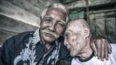 Mantan tahanan politik Diro Utomo (kiri) memeluk kawan senasibnya Slamet (kanan) di Pulau Buru. Pascapemilu 2019, mantan tahanan politk berharap siapapun presiden yang terpilih nanti dapat mengembalikan nama baik mereka. (ANTARA FOTO/Hafidz Mubarak A)
