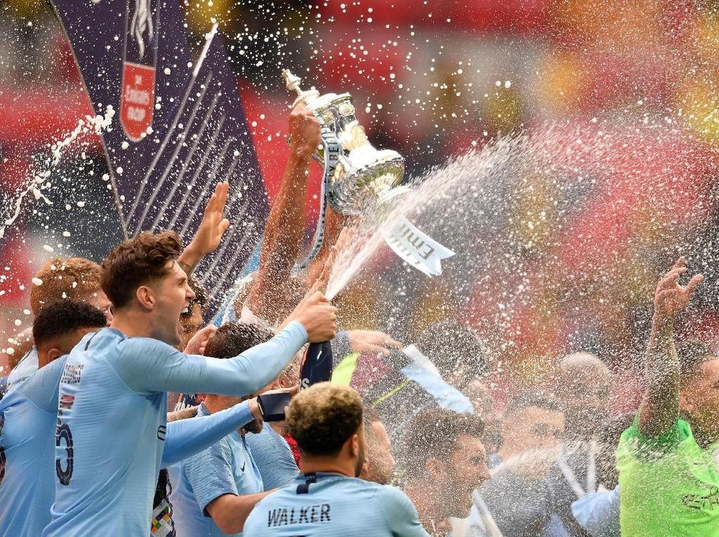 Seluruh pemain membuka tutup botol sampanye dan menyemprotkannya ke udara. (Foto: Toby Melville/Reuters)