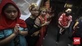Relawan wihara memakai bermacam baju adat daerah untuk menyambut para tamu yang datang menghadiri peringatan Hari Raya Waisak. (CNN Indonesia/ Hesti Rika)