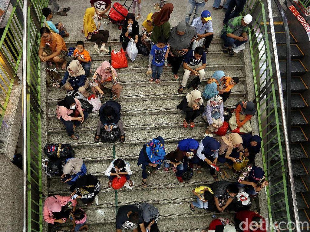 Sejumlah warga beristirahat di tangga setelah lelah berkeliling untuk mencari kebutuhan lebaran.