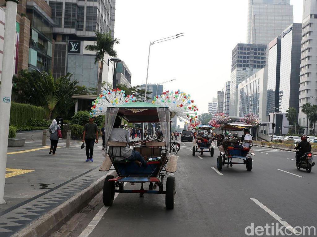 Beberapa delman melintas di antara kendaraan bermotor di Jalan Thamrin.