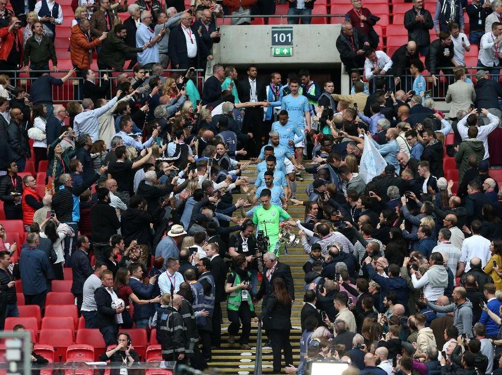 Seluruh tim Man City turun dari podium penyerahan trofi dan melanjutkan pesta di lapangan. (Foto: Alex Morton/Getty Images)